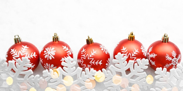 Рождественские красные шары со снежинками на белом фоне и золотые огни