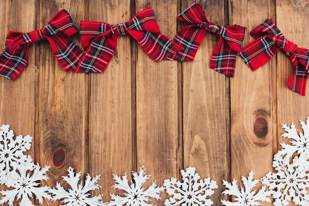 茶色の木にクリスマスの赤い弓と白い雪片。