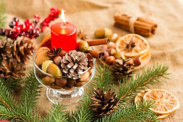 コーン、枝、applecols、どんぐりの装飾の構成のクリスマスの赤いろうそく。
