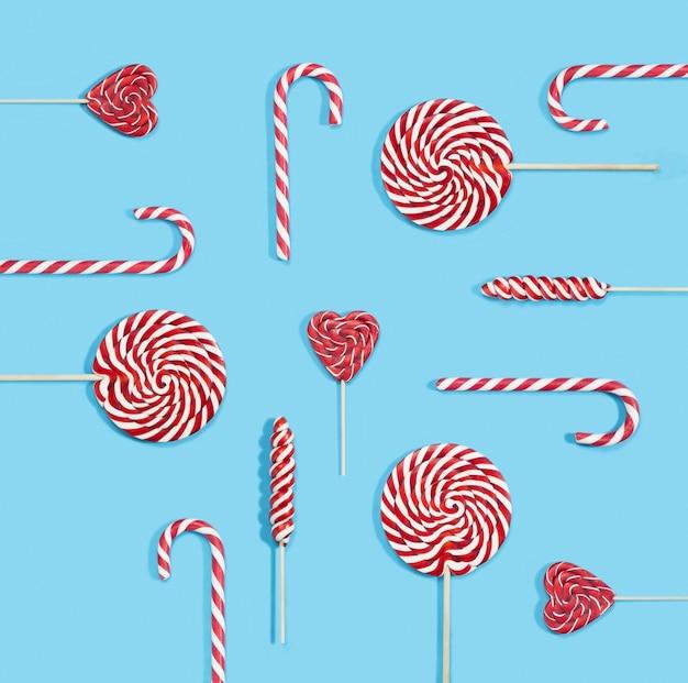 クリスマスの赤いキャンディケインと青い背景の上のロリポップパターン