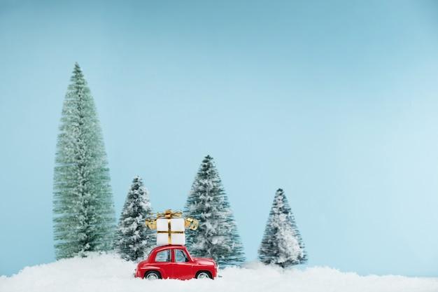 Рождественский красный автомобиль с подарочной коробкой в заснеженном сосновом лесу. открытка с новым годом