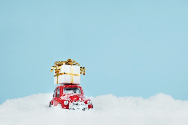 Christmas red car with a gift box in blue snowy landscape. happy new year card