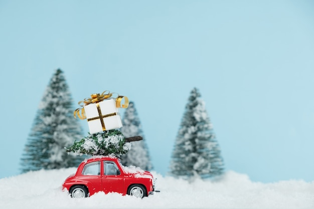 Christmas red car with a gift box in a snowy pine forest. happy new year card