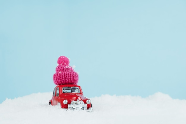 Christmas red car with knitted pink hat in a snowy landscape. space for text. happy new year