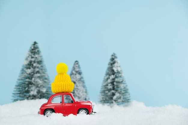 Christmas red car with knitted yellow hat in a snowy pine forest