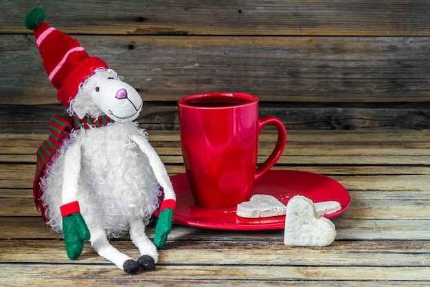Christmas, red cup with coffee and dessert on wooden table
