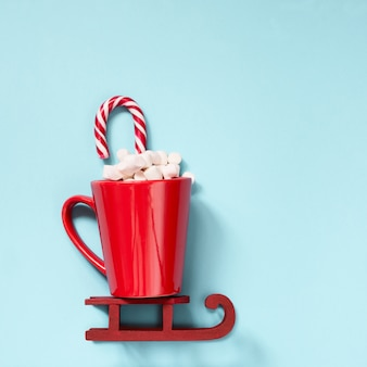 Christmas red cup with marshmallow and candy cane on red sleidge.