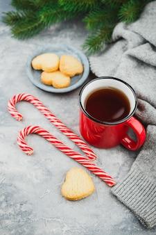 Рождественская красная эмалированная чашка чая, песочное сахарное печенье в форме сердечек, еловые ветки и леденцы на свете