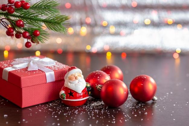 Новогодняя красная подарочная коробка, фигурка деда мороза, красные елочные шары, под еловой веткой. на темном столе со снегом и боке из гирлянд на светлом фоне боке.