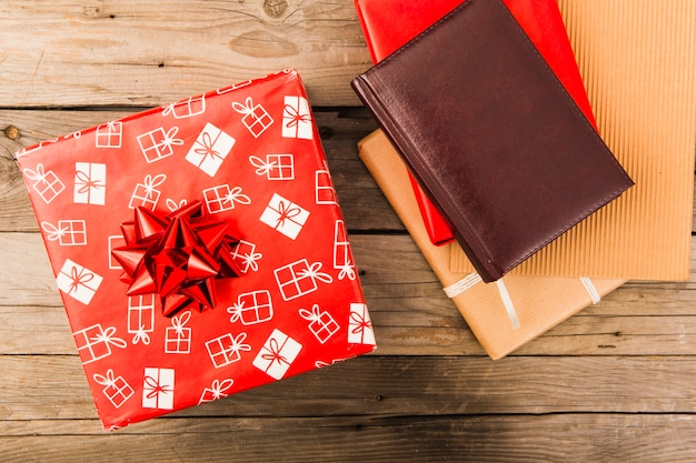 Christmas red gift box and leather notebook on table