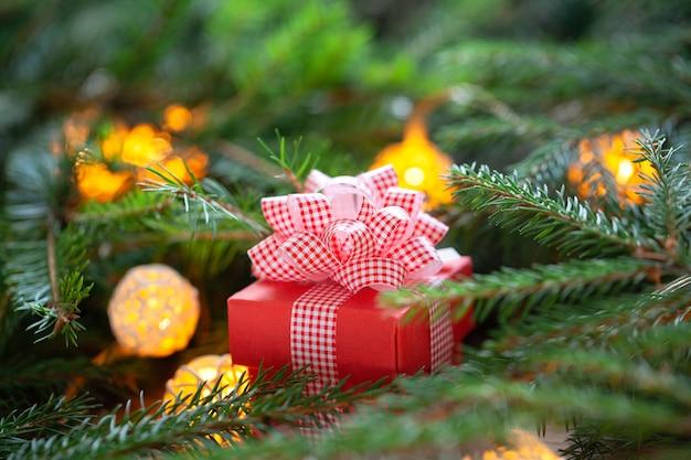 モミの枝に赤い弓とクリスマスの赤いギフトボックス