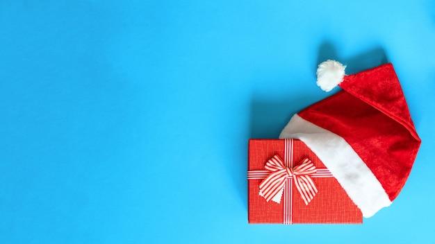 青い背景に分離されたサンタクロースの帽子の赤いリボンで飾られたクリスマスの赤い贈り物、クローズアップ、フラットレイ、コピースペース。