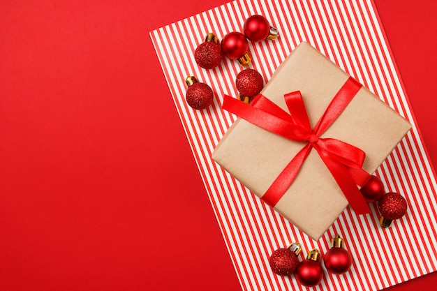 Christmas red glitter balls and craft paper gift on red background.