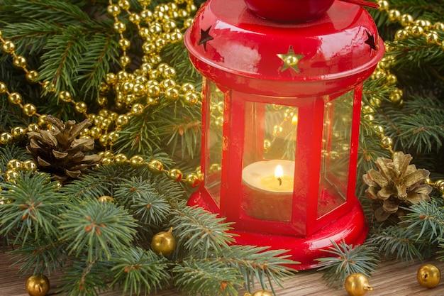 Рождественский красный светящийся фонарь крупным планом с вечнозеленым деревом