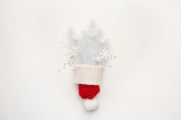 クリスマスの赤い帽子と白いモミの枝と雪片