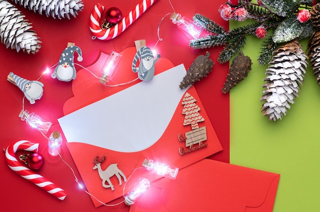 크리스마스 사탕과 크리스마스 불빛 빨간색과 녹색 배경에 텍스트를위한 공간으로 크리스마스 빨간 편지 봉투