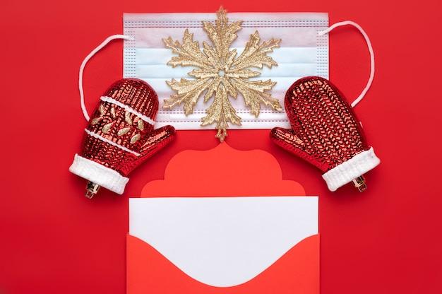 Рождественский красный конверт с буквами с пространством для текста на красном фоне, а также медицинская маска как символ безопасности