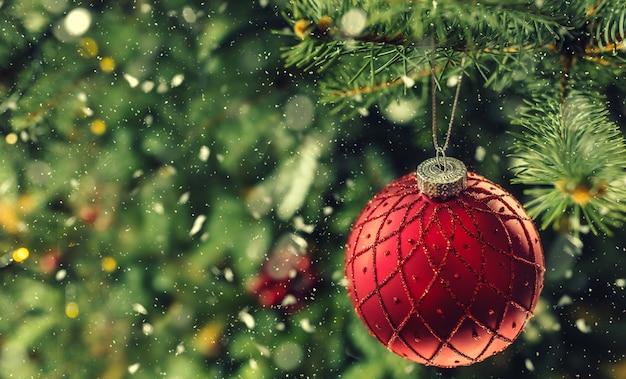 Рождественский красный роскошный шар на ветвях деревьев в снежной атмосфере.