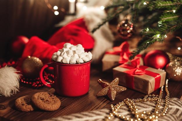 木製のテーブルにココアとマシュマロとクッキーとクリスマスの赤いマグカップ。クリスマスツリー、サンタの帽子、お祭りの装飾が施された新年の静物。