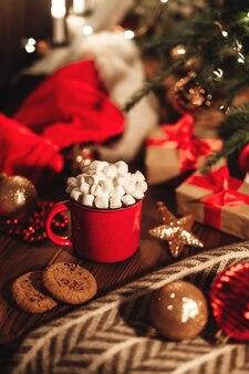 Рождественская красная кружка с какао и зефиром и печеньем на деревянном столе. новогодний натюрморт с елкой, шапкой санты и праздничными украшениями.
