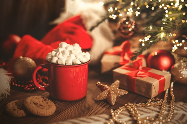 Christmas red mug with cocoa and marshmallows and cookies on a wooden table.