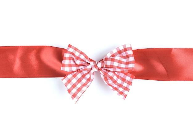 Рождественский бант из красной ленты в коробке, изолированной на белой поверхности