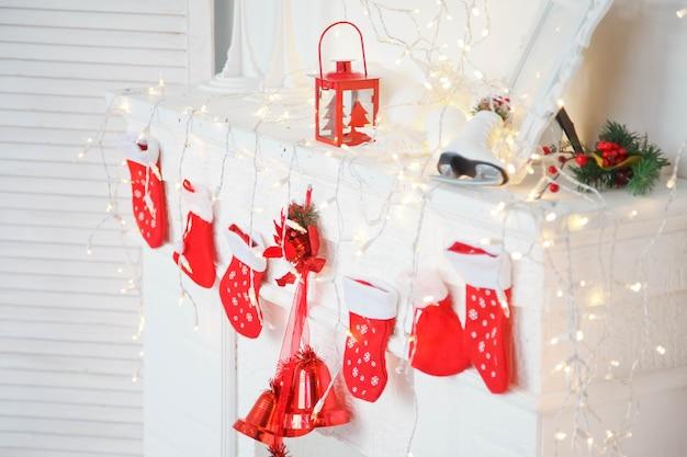 선물용 크리스마스 빨간 양말은 대가족의 hoñœñƒ에 있는 흰색 벽난로에 매달려 있습니다.