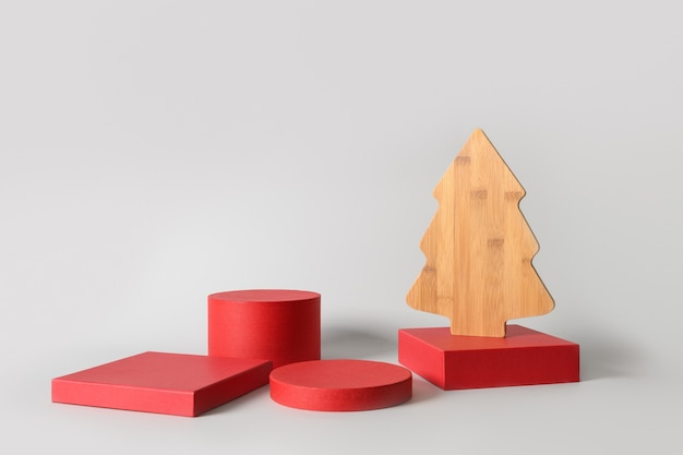 Christmas red stands with gift and decorative wooden creatuive xmas tree. modern podium background.