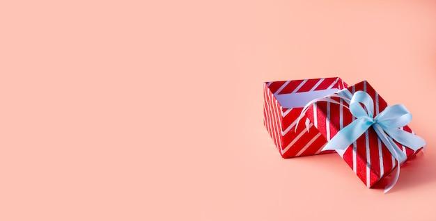 ピンクのスペースにクリスマスレッドストライプギフトボックス。クリエイティブなミニマルコンポジション。バナー。
