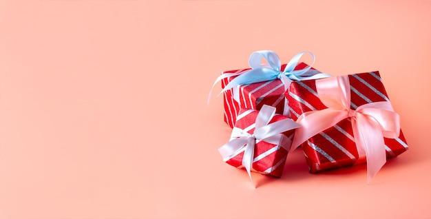 Christmas red striped gift boxes on pink background. creative minimal composition.
