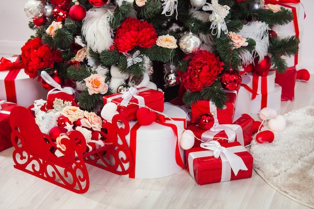 Christmas, red and white color presents under christmas tree