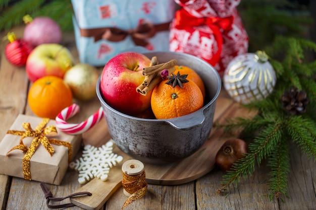 크리스마스 레드 와인 mulled 와인 향신료와 과일 나무 테이블에. 크리스마스를위한 전통적인 뜨거운 음료. 감귤, 사과, 냄비에 향미료 mulled 와인.