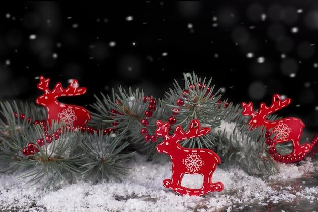 雪と黒の背景にトウヒの枝とクリスマスの赤い木製の鹿。