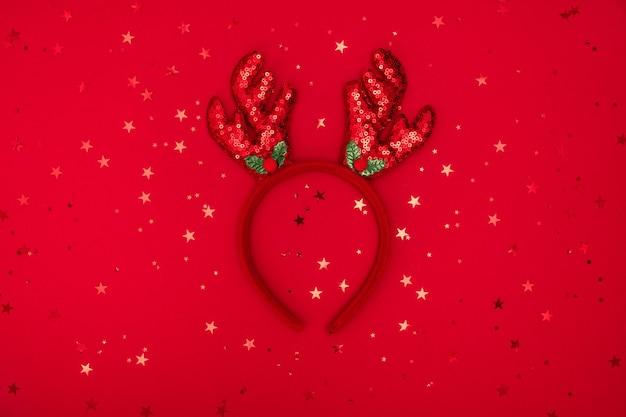 赤いキラキラの表面、グリーティングカードにクリスマストナカイの角のヘッドバンド。