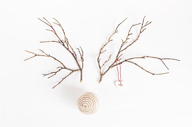 분기와 크리스마스 값싼 물건으로 만든 크리스마스 순록 개념. 미니멀리스트 겨울 계절 아이디어. 평면 위치, 평면도 구성