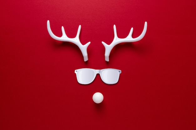 선글라스와 흰색 뿔로 만든 크리스마스 순록 얼굴
