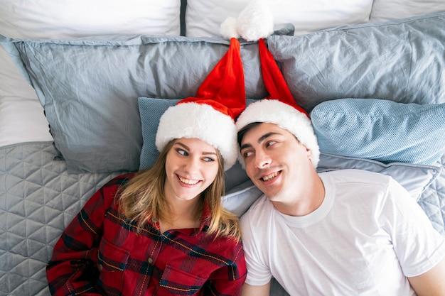 クリスマスの関係と家の概念若い異性愛者のカップルはサンタの帽子のベッドに横たわっています