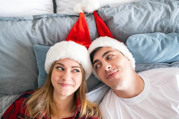 クリスマスの関係と家の概念若い異性愛者のカップルはサンタのクリスマスの帽子のベッドに横たわっています