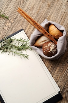 Christmas restaurant menu clipboard with copy space for text. blank paper clipboard with christmas tree branch and bread on wooden table background