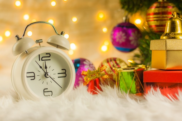 Christmas retro alarm clock decorated with gift box and fir festive on blurred bokeh background