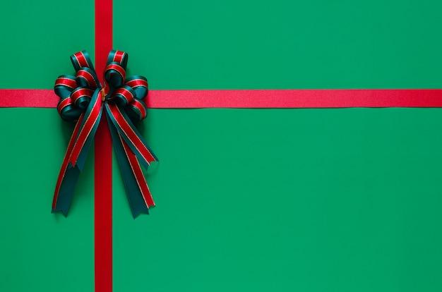 Рождественская лента с бантом на зеленом фоне. рождество и новый год концепция.