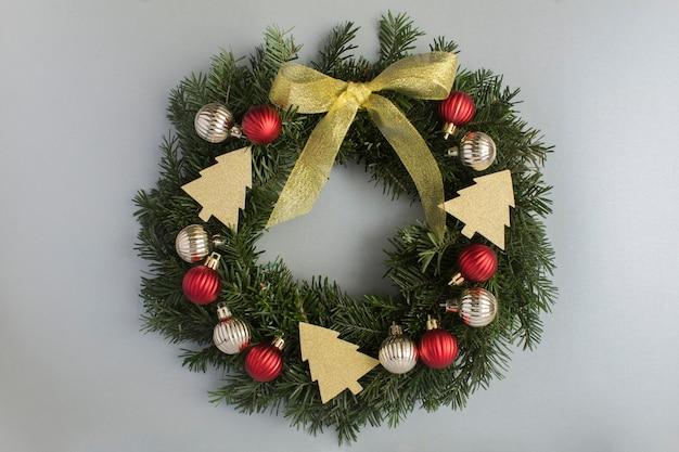 灰色の背景に赤と金のボールとクリスマスリングまたは花輪。上面図。閉じる。