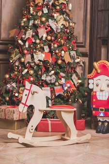 Интерьер комнаты украшения рождества с стулом лошади, новогодней елкой и щелкунчиком.