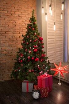 Дизайн интерьера новогодней комнаты в стиле лофт с красной кирпичной стеной и рождественской елкой, украшенной подарками
