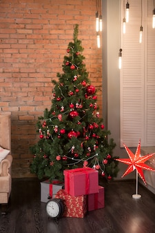 Christmas room loft interior design with red brick wall with xmas tree decorated by presents