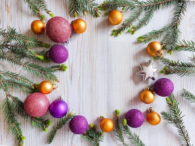 クリスマスラウンドフレーム。モミの枝と明るい金、紫、銀の光沢のあるボールと星