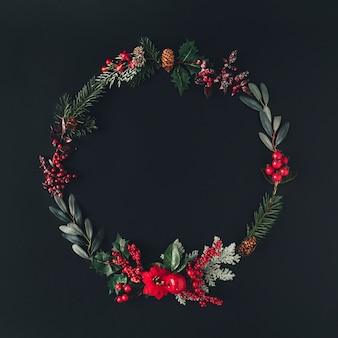 어두운 칠판에 자연 겨울 것 들으로 만든 크리스마스 라운드 프레임.