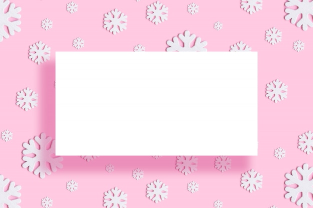 Christmas round frame made of white decor holiday snowflakes on pink background