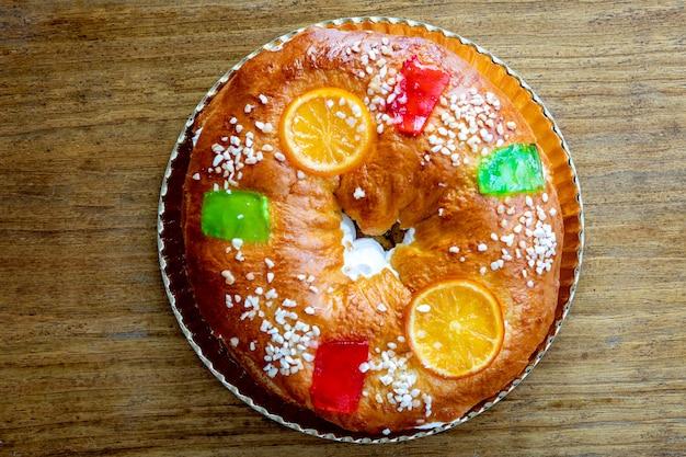 Рождественский круглый фруктовый торт, украшенный еловой веткой, глазированными фруктами и орехами на деревянном столе.