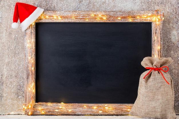 Рождественский деревенский фон - старинные планки из дерева с огнями и рождественскими украшениями.